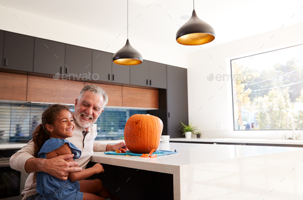 Grandfather And Granddaughter Carving Halloween Lantern From Pumpkin At Home - Stock Photo - Images
