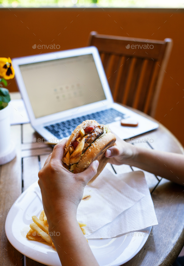 Lunch break with cheeseburger. Smart working concept during quarantine due to Coronavirus covid-19. - Stock Photo - Images
