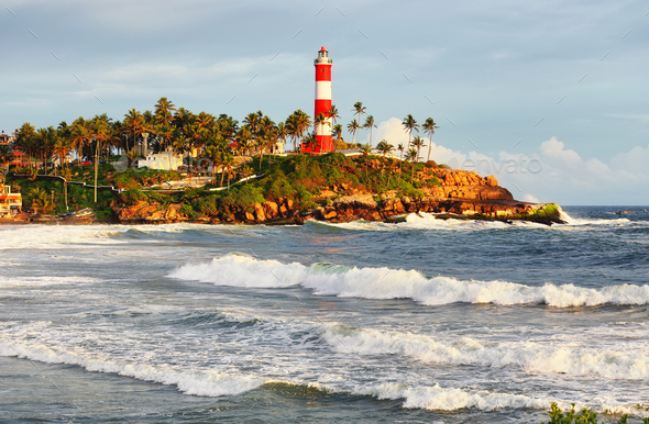 Lighthouse on the rocks near the ocean in Kovalam, Kerala, India - Stock Photo - Images