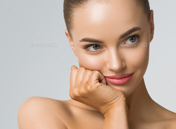 Clean skin woman face close up skin beauty tanned face beautiful smile over blue background - Stock Photo - Images