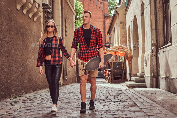 Handsome skater and his girlfriend walking around an old narrow streets of Europe. - Stock Photo - Images