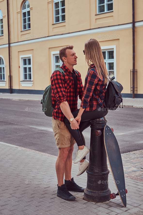 Handsome skater holding hands his girlfriend who sitting on a fire hydrant in an old Europe street. - Stock Photo - Images