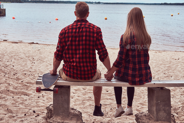 Back view of a cute hipster couple, sits on a bench in the middle of the beach and watch a sea. - Stock Photo - Images