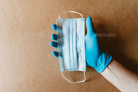 Hand in blue rubber gloves holds a medical mask. Health care and antivirus protection concept - Stock Photo - Images
