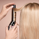 The hairdresser curls long hair with a Curling iron - PhotoDune Item for Sale