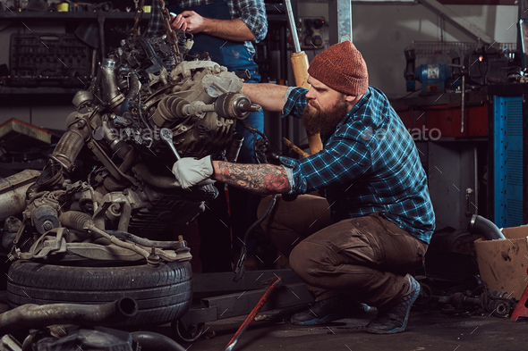 Brutal tattooed mechanic repairs the car engine in the garage. Service station. - Stock Photo - Images