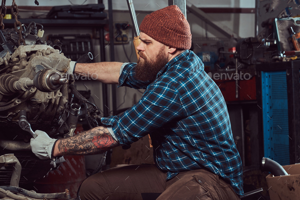 Brutal tattooed mechanic repairs the car engine which is raised on the hydraulic lift in the garage - Stock Photo - Images