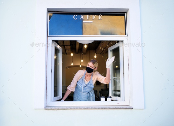 Woman with face mask serving coffee through window, shop open after lockdown - Stock Photo - Images