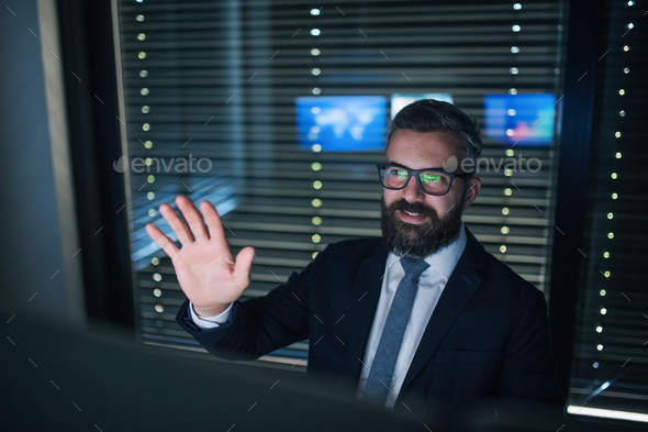 Front view of businessman having video call with colleague at desk - Stock Photo - Images