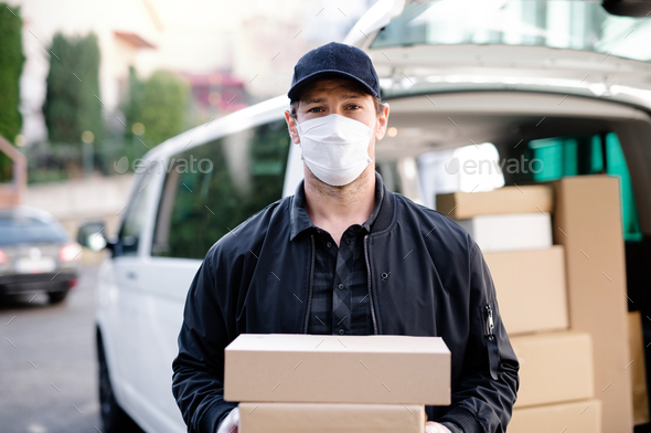 Delivery man courier with face mask delivering parcel boxes in town - Stock Photo - Images