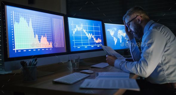 Frustrated businessman with computer sitting at desk, working late. Financial crisis concept - Stock Photo - Images