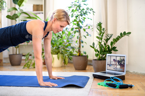 Woman indoors doing fitness workout at home, watching online video tutorial - Stock Photo - Images