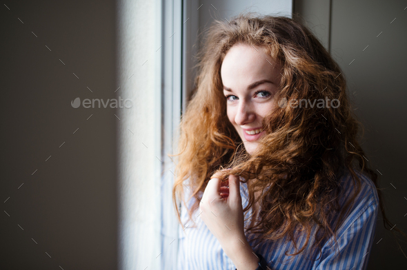 Close-up portrait of young woman standing by window indoors at home - Stock Photo - Images