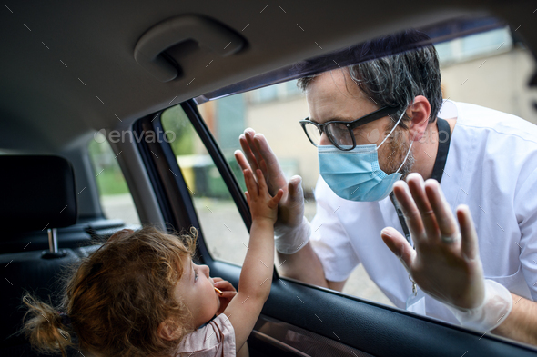 Doctor coming to see daughter in isolation, car window glass separating them - Stock Photo - Images
