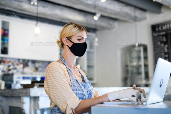 Coffee shop woman owner working with face mask, open after lockdown quarantine - Stock Photo - Images