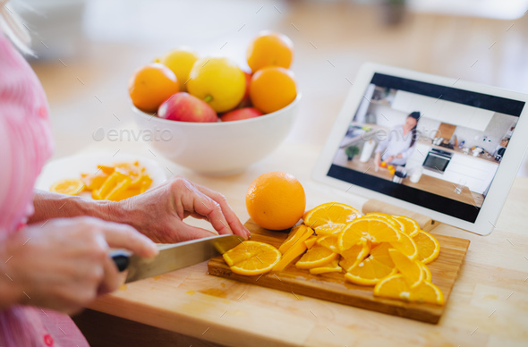 Unrecognizable woman preparing food in kitchen indoors, following food vlogger - Stock Photo - Images