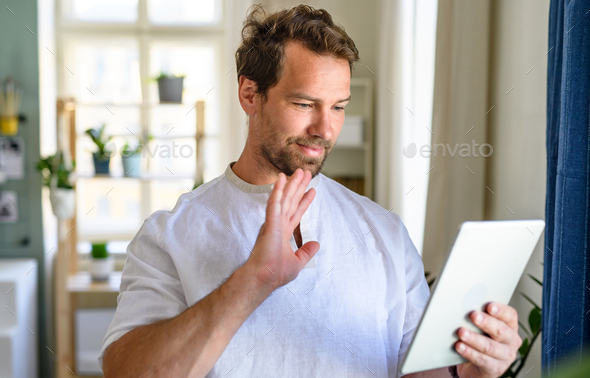 Portrait of mature man having video call on tablet at home - Stock Photo - Images