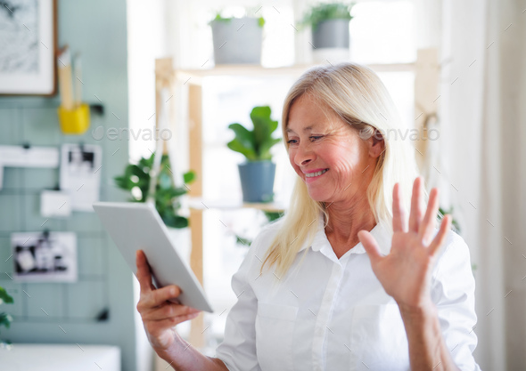 Senior businesswoman with tablet indoors in home office, business call concept - Stock Photo - Images