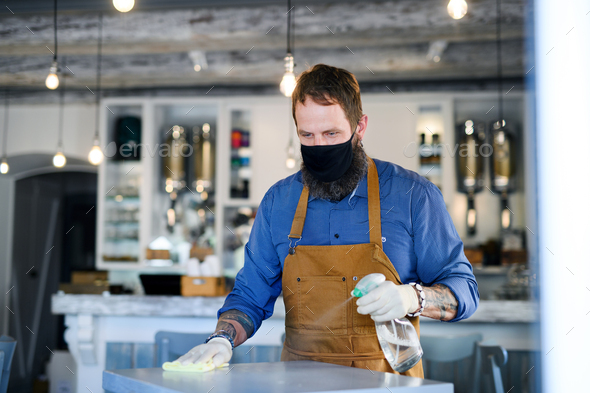 Coffee shop man owner working with face mask and gloves, disinfecting tables - Stock Photo - Images