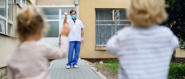 Children greeting father doctor from distance in front of hospital, coronavirus concept - Stock Photo - Images