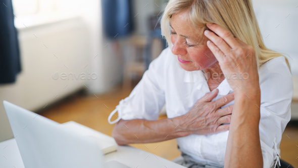Frustrated woman engineer with laptop indoors in home office, feeling pain - Stock Photo - Images