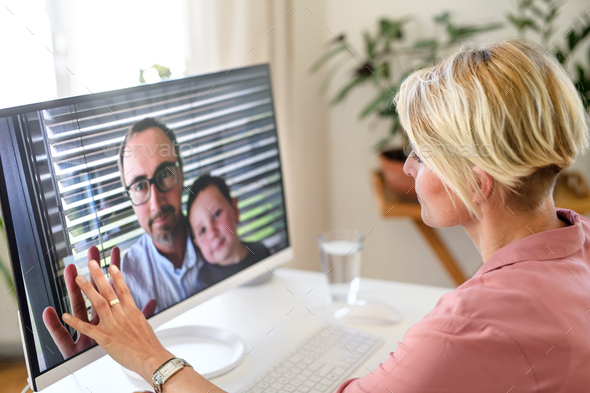 Young woman having video call with husband and son, social distancing concept - Stock Photo - Images