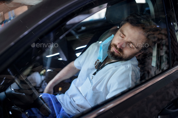 Tired and exhausted doctor sitting in car after long and difficult shift, sleeping - Stock Photo - Images
