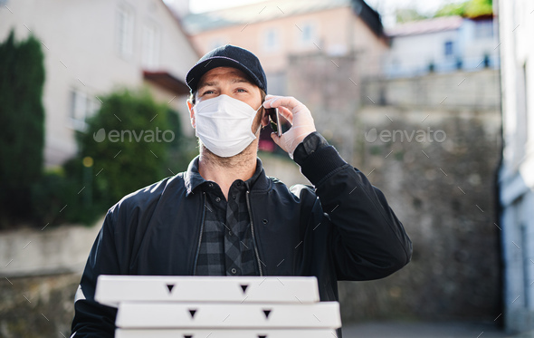 Delivery man courier with smartphone and face mask delivering pizza in town - Stock Photo - Images
