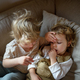 Two small sick children brother and sister at home lying in bed - PhotoDune Item for Sale