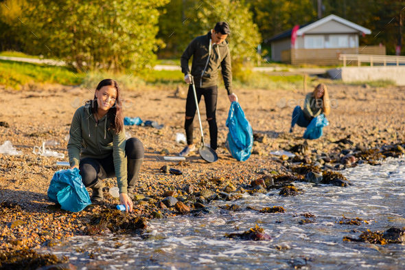 Young woman in a team picking up garbage in bag at beach - Stock Photo - Images