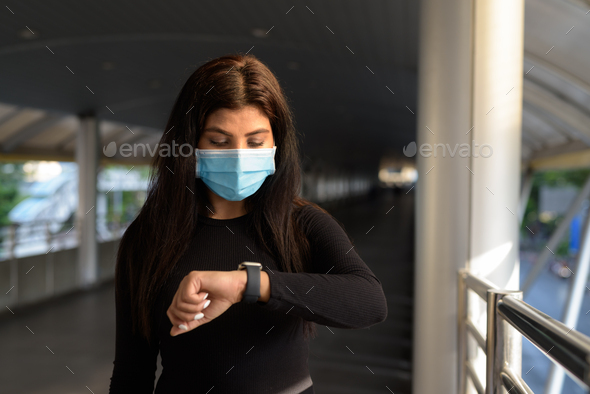 Young Indian woman with mask checking the time at footbridge in the city - Stock Photo - Images