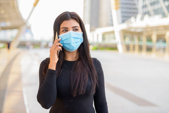 Young Indian woman with mask talking on the phone at the skywalk bridge - Stock Photo - Images