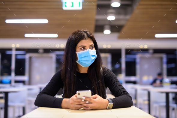Young Indian woman with mask thinking while using phone and sitting with distance at food court - Stock Photo - Images
