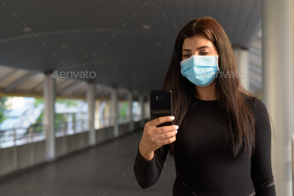 Young Indian woman with mask using phone at the footbridge - Stock Photo - Images
