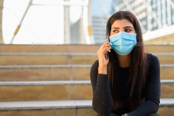 Young Indian woman with mask talking on the phone and sitting by the stairs in city - Stock Photo - Images