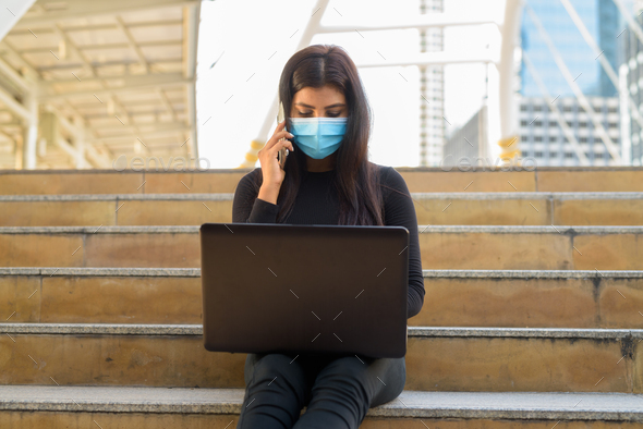 Young Indian woman with mask using laptop and talking on the phone in the city - Stock Photo - Images