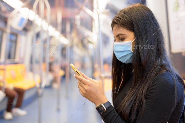 Young Indian woman with mask using phone and sitting with distance inside the train - Stock Photo - Images