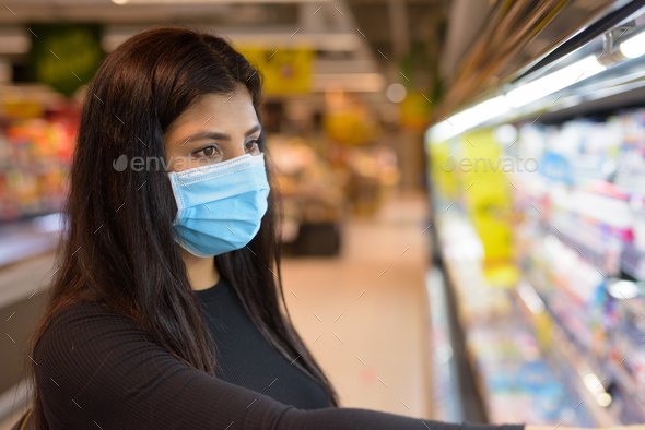 Face of young Indian woman with mask shopping with distance at the supermarket - Stock Photo - Images
