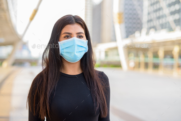 Young Indian woman with mask for protection from corona virus outbreak at the skywalk bridge - Stock Photo - Images