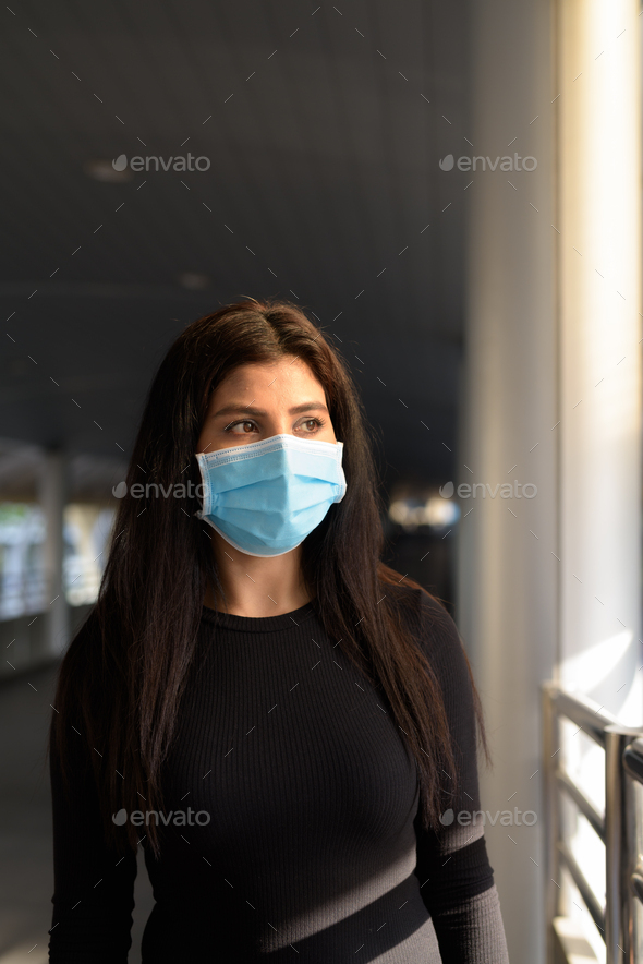Young Indian woman thinking with mask for protection from corona virus outbreak at the footbridge - Stock Photo - Images