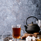 A black metal teapot and a cup of tea in glass cup - PhotoDune Item for Sale