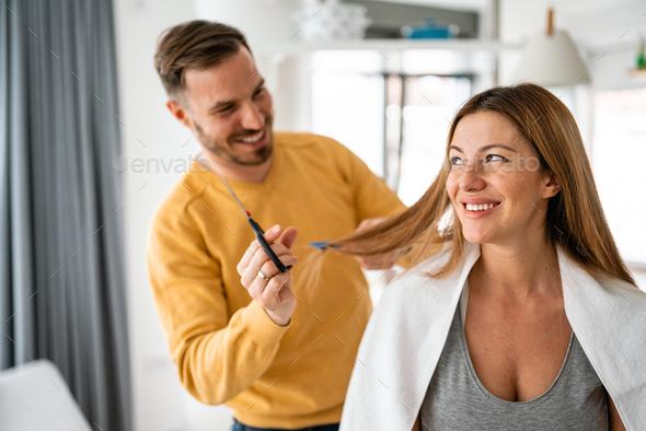 Self hair care during quarantine. Couple having hair cut at home isolation coronavirus pandemic - Stock Photo - Images