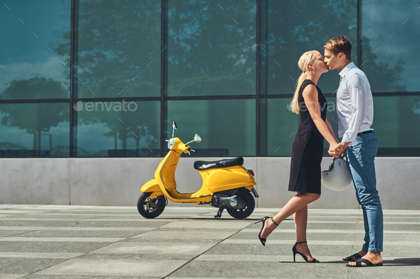 Attractive couple in love - near a yellow classic Italian scooter against a skyscraper. - Stock Photo - Images