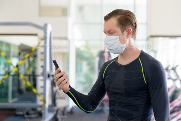 Profile view of young man with mask using phone at gym during corona virus covid-19 - Stock Photo - Images