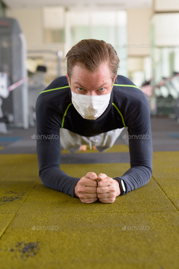 Face of young man with mask doing plank position on the floor at gym during corona virus covid-19 - Stock Photo - Images