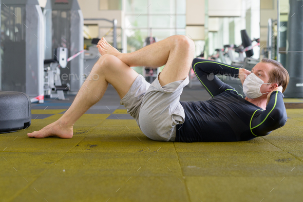 Full body shot of young man with mask doing sit ups on the floor at gym during corona virus covid-19 - Stock Photo - Images