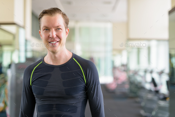 Portrait of happy young handsome man thinking at the gym during covid-19 - Stock Photo - Images