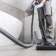 Man Vacuuming White Tile Floor In Bathroom. - PhotoDune Item for Sale