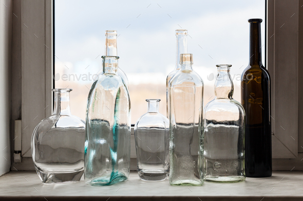 many empty bottles on windowsill and view of park - Stock Photo - Images