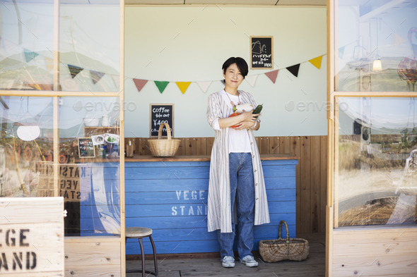 Japanese woman standing in a farm shop, holding vegetables, smiling at camera. - Stock Photo - Images